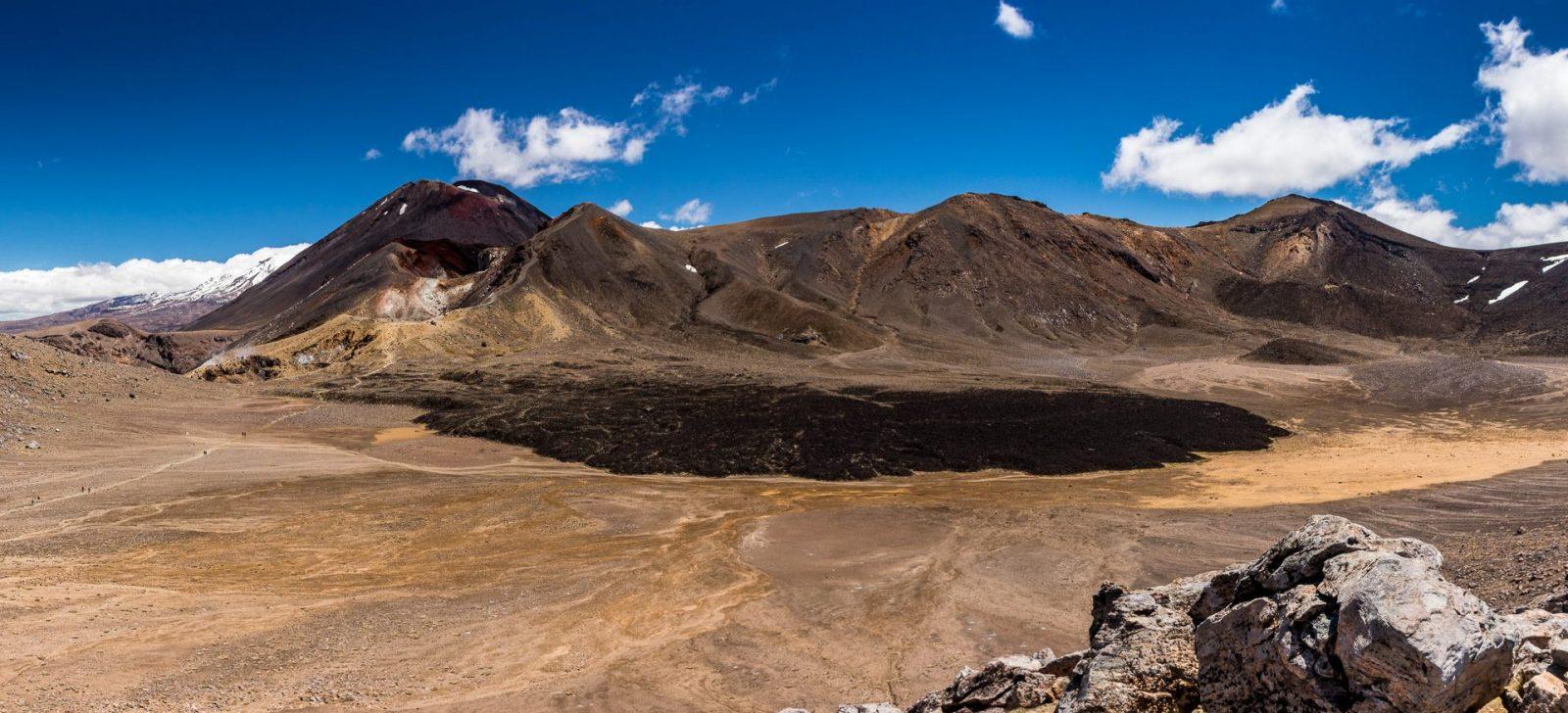 Dominantní horou je tu tmavá Ngauruhoe, napravo od ní oblý vrchol Tongariro a vzadu vystupují zasněžené svahy Ruapehu. V popředí černé lávové pole